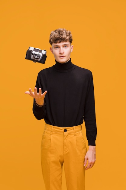 Uomo con una macchina fotografica in una scena gialla Foto Gratuite
