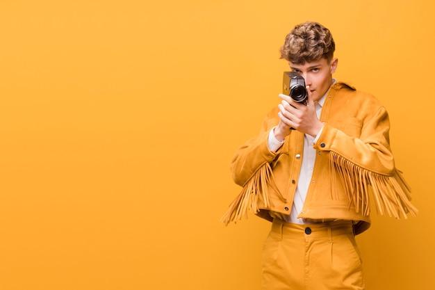 Uomo con una videocamera in una scena gialla Foto Gratuite