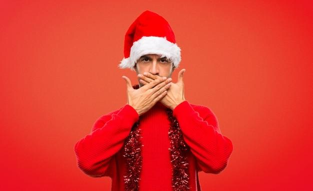 Uomo con vestiti rossi che celebra le feste di natale che coprono la bocca con le mani Foto Premium