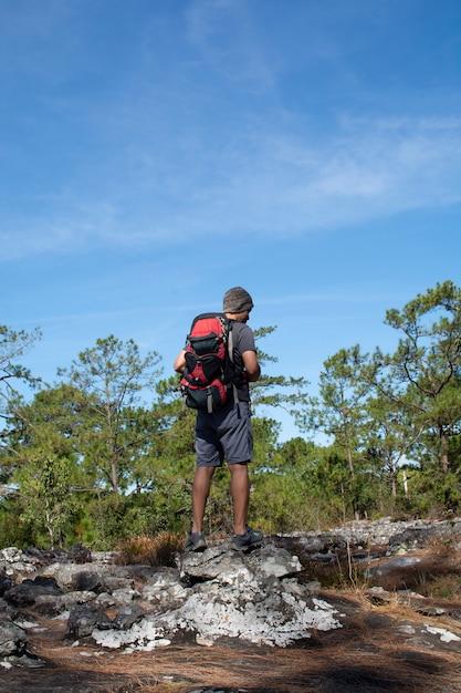Uomo con zaino in piedi sulla scogliera, guardando la foresta con cielo blu Foto Premium
