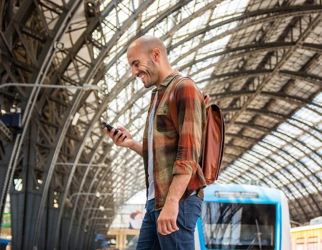 Uomo con zaino utilizzando mobile Foto Gratuite
