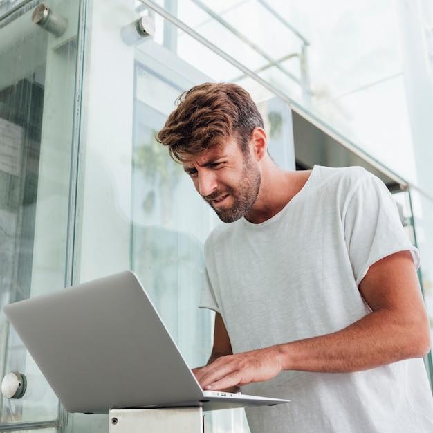 Uomo confuso che controlla dispositivo portatile Foto Gratuite