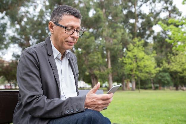 Uomo contento che utilizza smartphone e che si siede sul banco nel parco Foto Gratuite