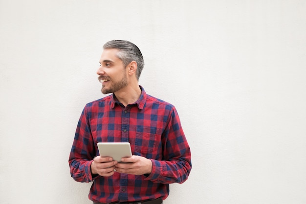 Uomo contento con la compressa digitale che guarda da parte Foto Gratuite