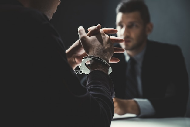 Uomo criminale con le manette che sono intervistate nella stanza di interrogatorio Foto Premium