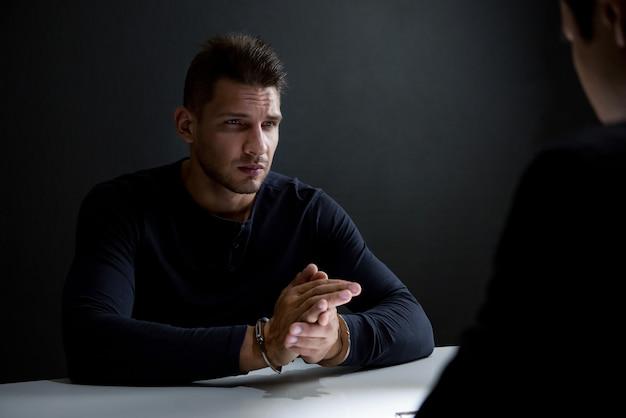 Uomo criminale con le manette nella stanza degli interrogatori Foto Premium