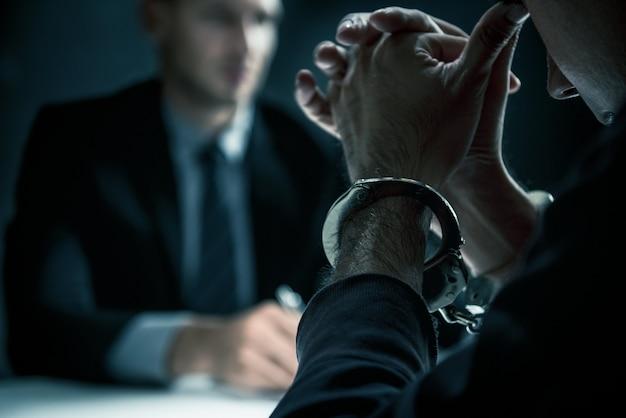 Uomo criminale con le manette nella stanza di interrogatorio Foto Premium