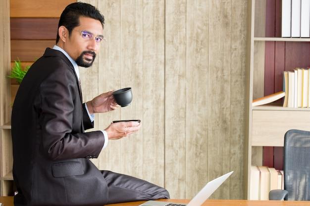 Uomo d'affari adulto che si siede sullo scrittorio e che tiene la tazza di caffè. Foto Premium