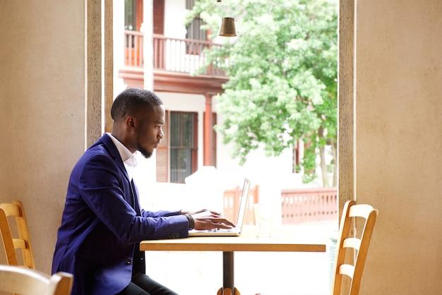 Uomo d'affari africano che si siede con il computer portatile al caffè Foto Premium