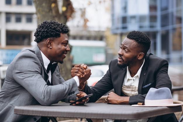 Uomo d'affari africano due che si siede fuori del caffè Foto Gratuite