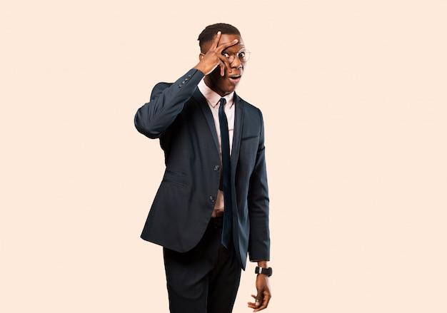 Uomo d'affari afroamericano che sembra scosso, spaventato o terrorizzato, coprendo il viso con la mano e sbirciando tra le dita contro la parete beige Foto Premium