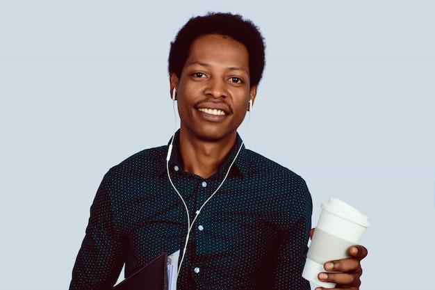 Uomo d'affari afroamericano con le cartelle e caffè. Foto Premium