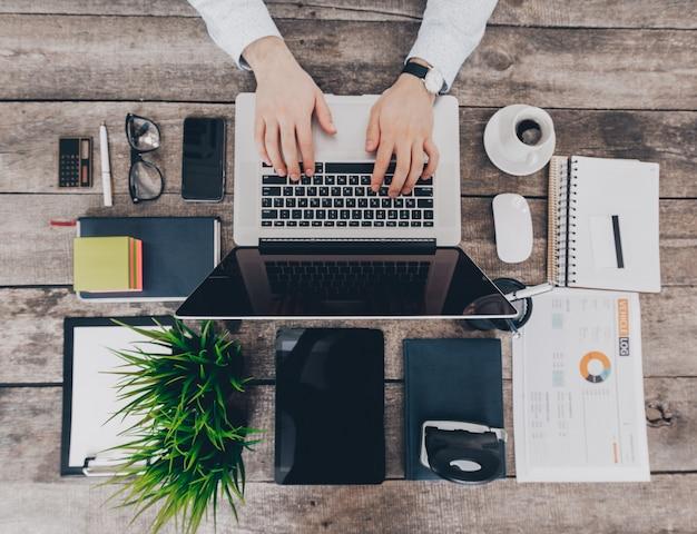 Uomo d'affari al lavoro. vista superiore del primo piano dell'uomo che lavora al computer portatile Foto Premium