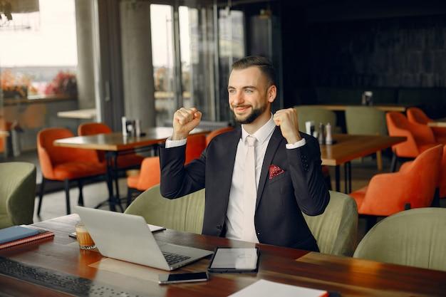 Uomo d'affari alla moda che lavora in un caffè Foto Gratuite
