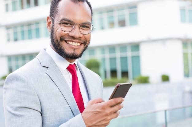 Uomo d'affari allegro felice con gli smartphones che posano all'aperto Foto Gratuite