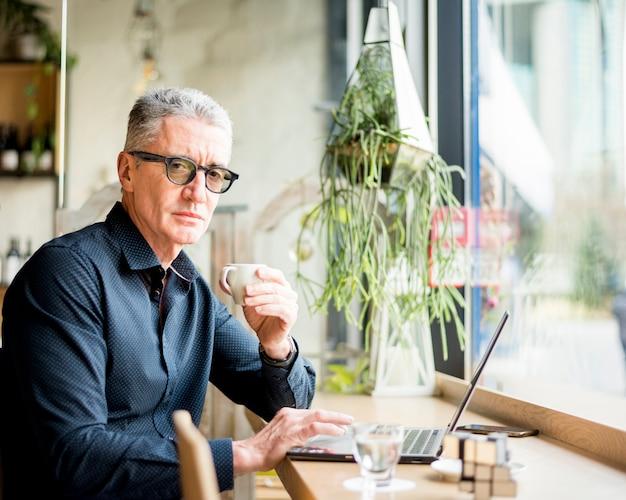 Uomo d'affari anziano che posa con il caffè Foto Gratuite