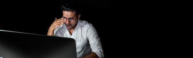 Uomo d'affari asiatico affaticato che ritiene assonnato e che sbadiglia mentre lavorando il turno di notte Foto Premium