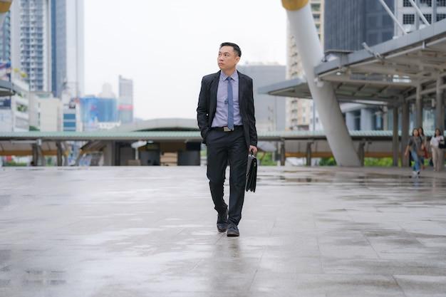 Uomo d'affari asiatico che cammina e che tiene cartella con gli edifici per uffici di affari Foto Premium