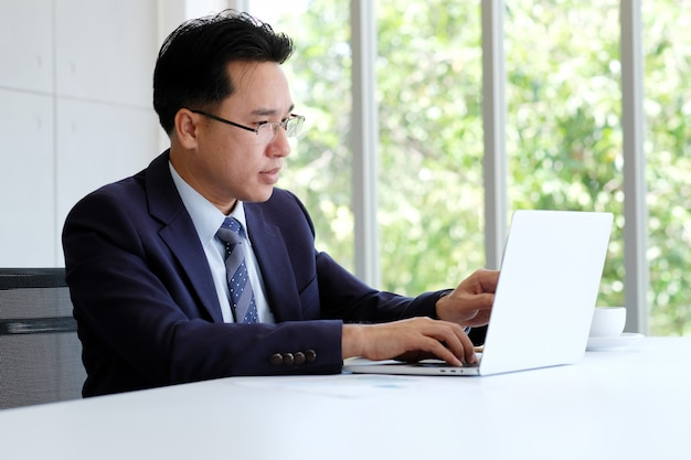 Uomo d'affari asiatico che lavora con il computer portatile all'ufficio Foto Premium