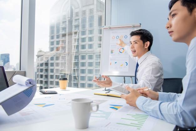 Uomo d'affari asiatico che presenta i grafici del business plan Foto Premium