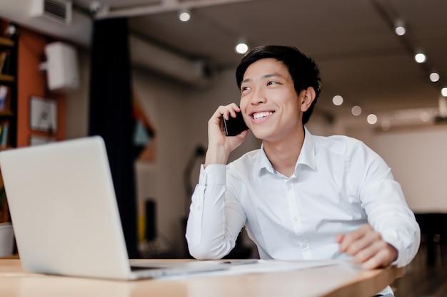 Uomo d'affari asiatico millenial sorridente che parla sul telefono nell'ufficio della società con il computer portatile Foto Premium