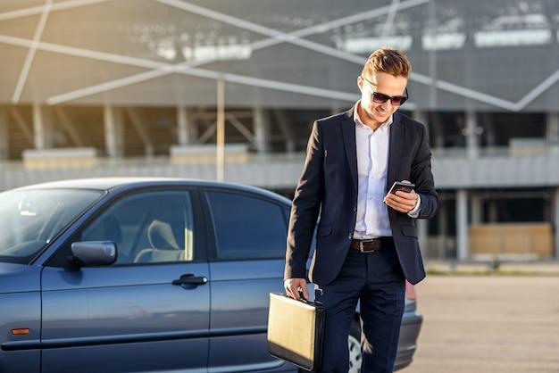 Uomo d'affari bello attraente con il diplomatico e lo smartphone nelle mani vicino all'automobile Foto Premium