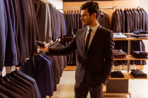 Uomo d'affari bello che guarda e che sceglie vestito classico. Foto Premium