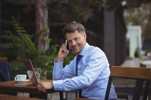Uomo d'affari bello che parla sul telefono cellulare mentre per mezzo del computer portatile Foto Premium