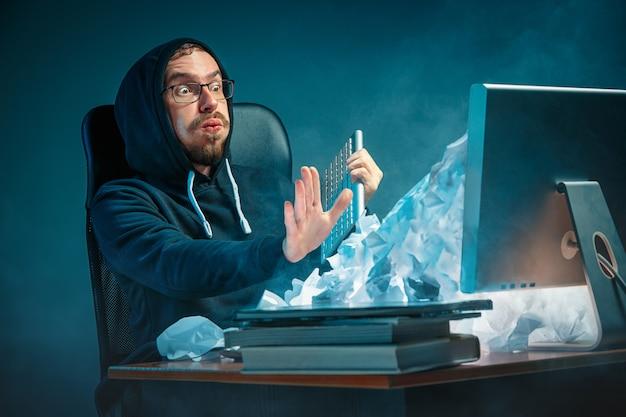 Uomo d'affari bello sollecitato giovani che lavora allo scrittorio in ufficio moderno che grida allo schermo del computer portatile e che è arrabbiato per lo spam Foto Gratuite