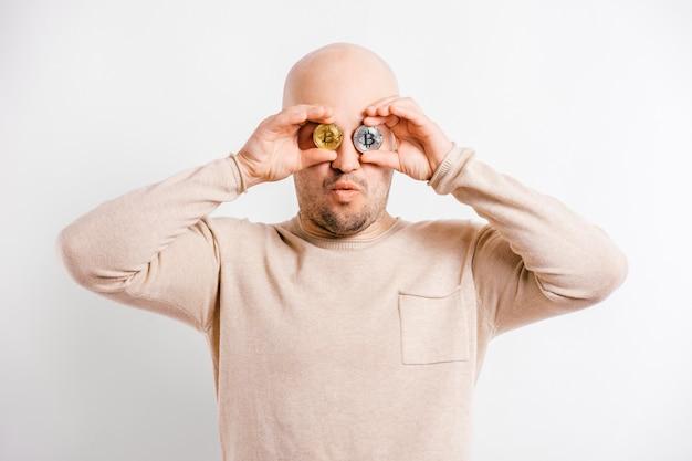 Uomo d'affari calvo felice che gioca con le monete del bitcoin davanti agli occhi. ritratto divertente del minatore della blockchain isolato su bianco Foto Premium