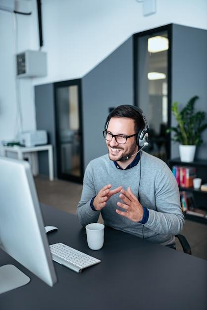 Uomo d'affari casuale che ha una video chiamata in ufficio moderno. Foto Premium