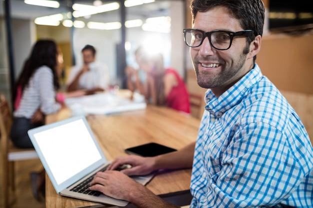 Uomo d'affari casuale che per mezzo di un computer portatile Foto Premium