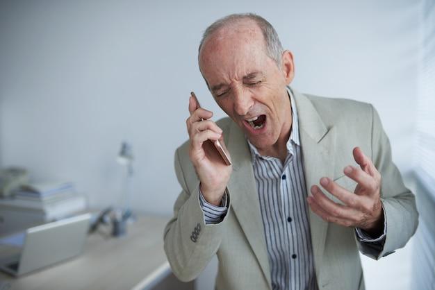Uomo d'affari caucasico calvo arrabbiato che tiene telefono cellulare e che grida con rabbia Foto Gratuite
