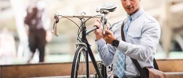 Uomo d'affari caucasico goto work con la bicicletta nel giorno libero dell'automobile nella città - stile di vita urbano Foto Premium