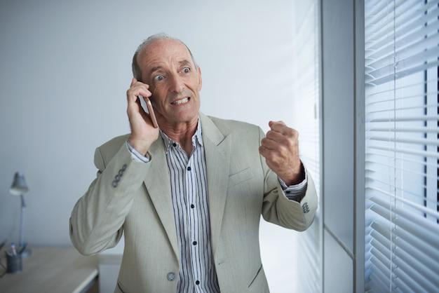 Uomo d'affari caucasico maturo arrabbiato che parla sul telefono in ufficio e che stringe pugno Foto Gratuite