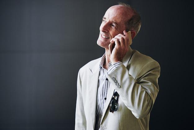 Uomo d'affari caucasico maturo che posa nello studio e che parla sul telefono cellulare Foto Gratuite