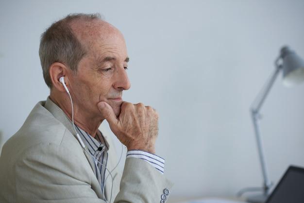 Uomo d'affari caucasico senior che si siede nell'ufficio con le cuffie e che esamina computer portatile Foto Gratuite