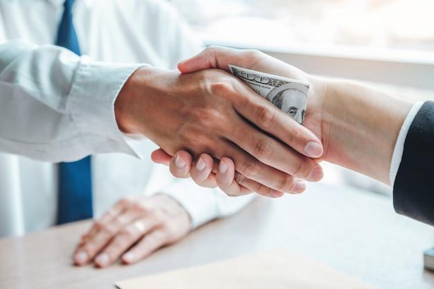 Uomo d'affari che agita le mani che danno le banconote in dollari al direttore aziendale per trattare contratto Foto Premium