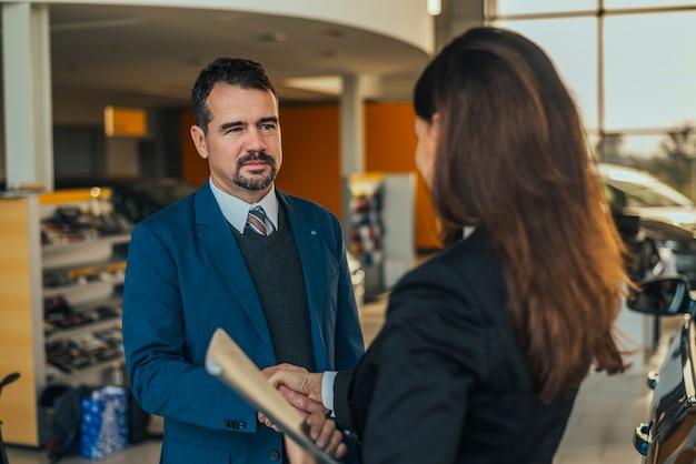 Uomo d'affari che agita le mani con il rivenditore di auto donna. Foto Premium