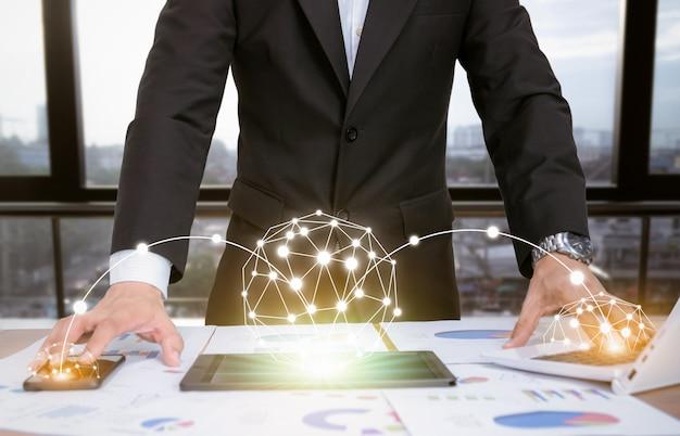 Uomo d'affari che analizza i grafici con i dispositivi tecnologici Foto Premium