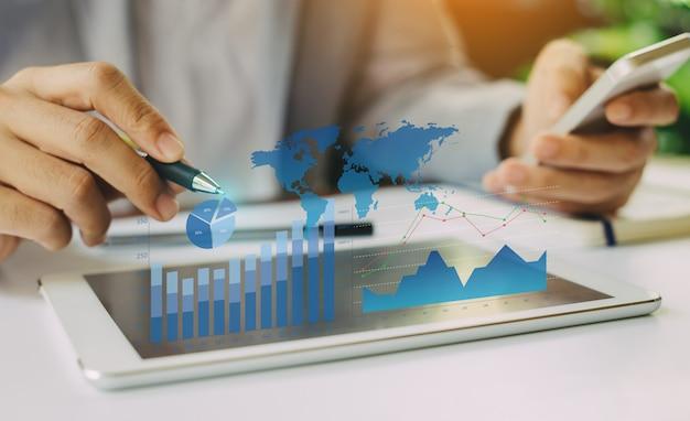 Uomo d'affari che analizza l'equilibrio del rapporto finanziario della società con i grafici aumentati digitali di realtà. Foto Premium