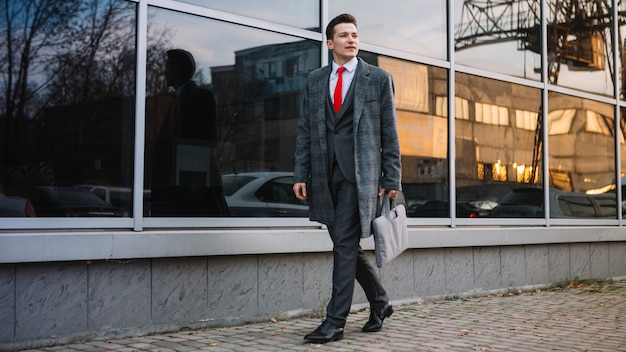 Uomo d'affari che cammina con una valigetta Foto Gratuite