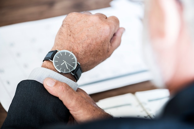Uomo d'affari che controlla orologio a disposizione Foto Gratuite
