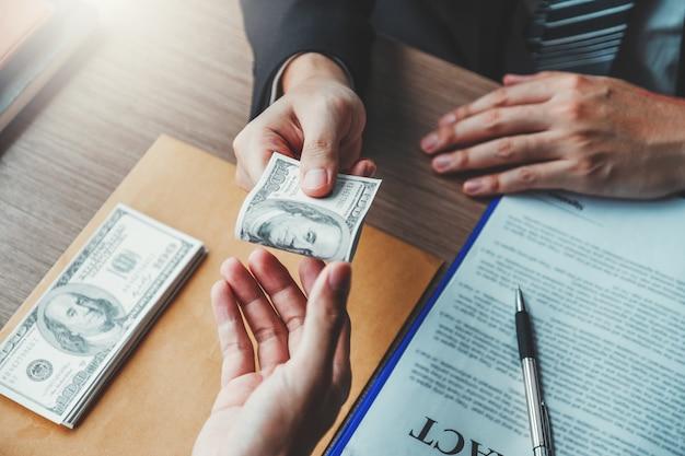 , uomo d'affari che dà le banconote in dollari al direttore aziendale per trattare il contratto Foto Premium