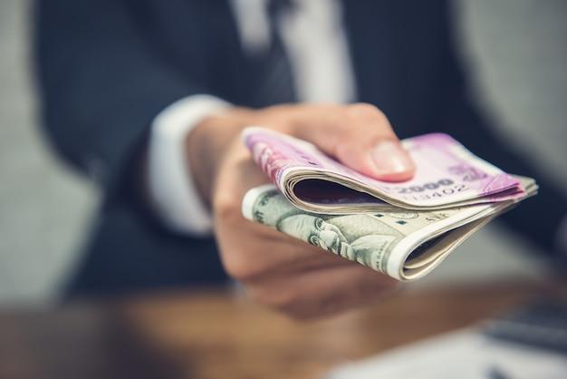 Uomo d'affari che dà soldi sotto forma di valuta di rupie indiane Foto Premium