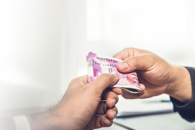 Uomo d'affari che dà soldi, valuta della rupia indiana, al socio di hs Foto Premium