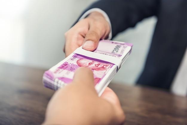 Uomo d'affari che dà soldi, valuta della rupia indiana, al suo compagno Foto Premium