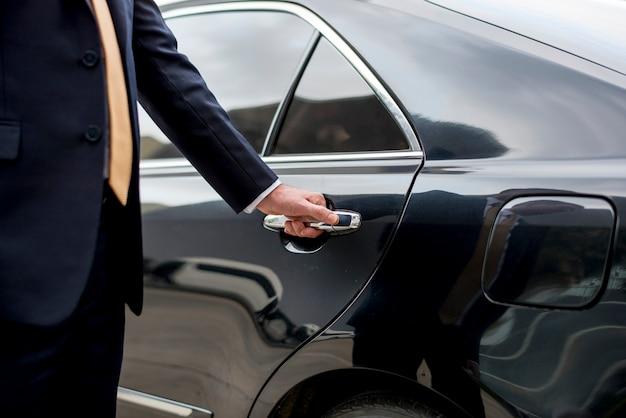 Uomo d'affari che entra nella sua auto Foto Premium