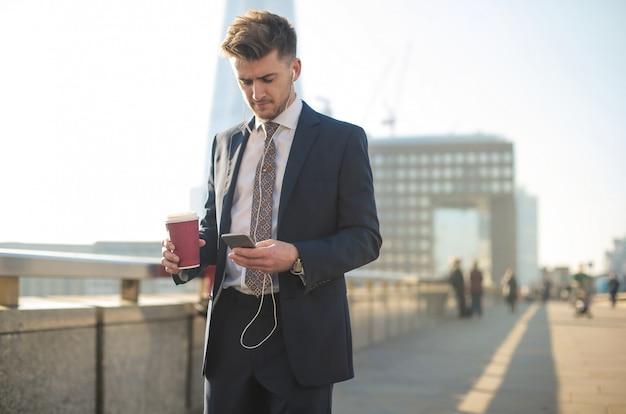 Uomo d'affari che ha una chiamata mentre camminando nella via Foto Premium