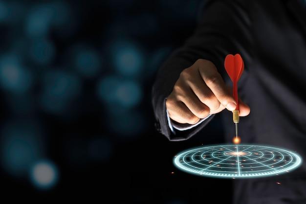 Uomo d'affari che lancia il dardo rosso della freccia al bordo di dardo virtuale dell'obiettivo. impostare obiettivi e target per il concetto di investimento aziendale. Foto Premium